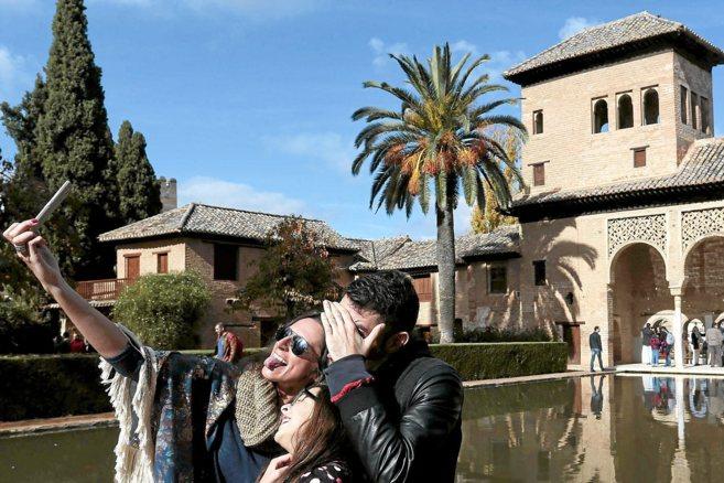 Dos visitantes se toman una foto en uno de los patios del Generalife.
