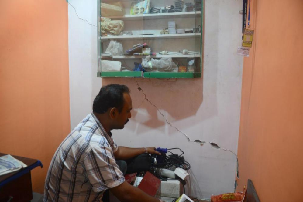 Un trabajador Indio en Siliguri observa los daños causados en su...