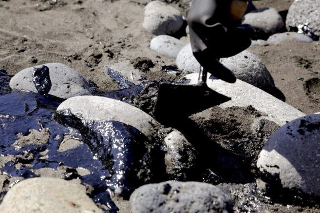 Personal de limpieza recogiendo el petróleo que ha llegado a la playa...
