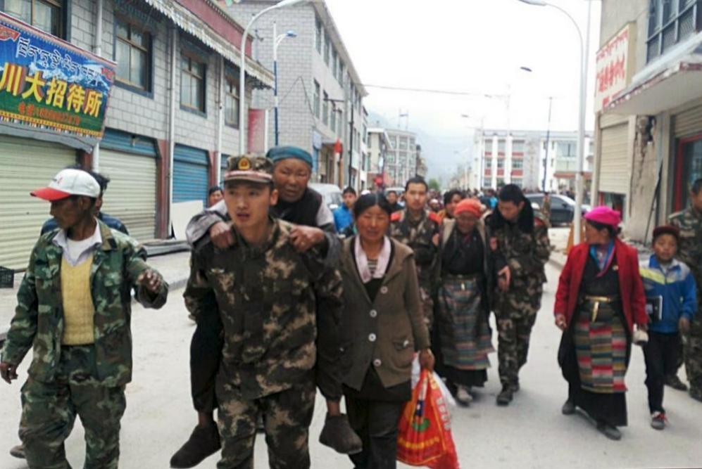 Soldados ayudando alas víctimas del terremoto a alcanzar una zona...