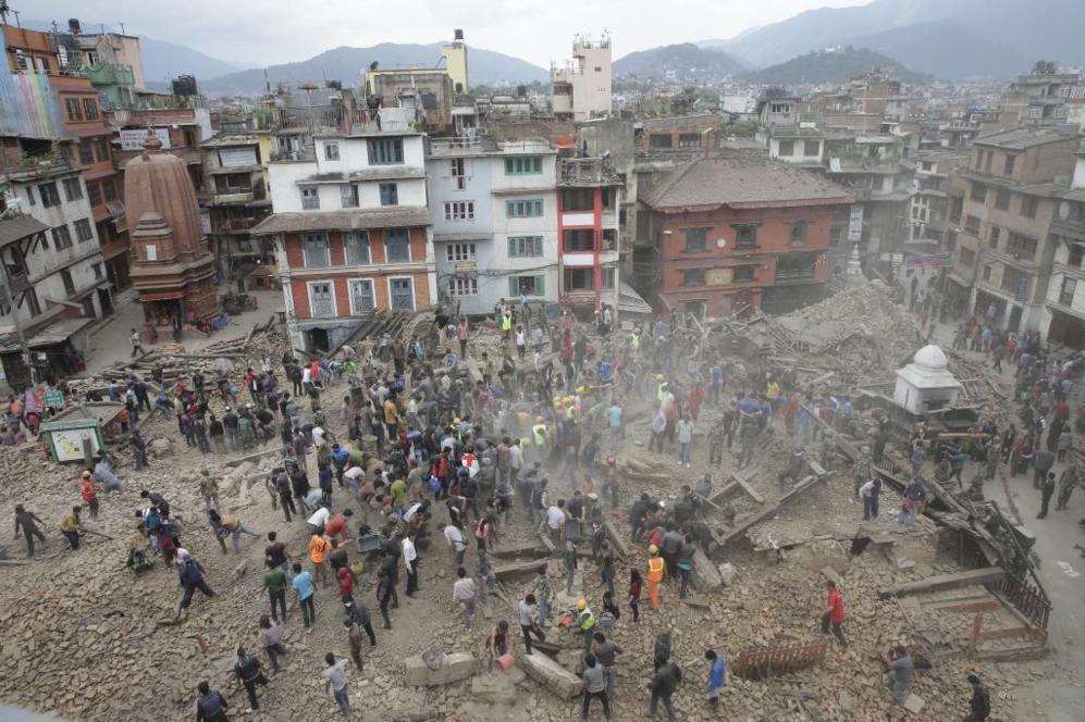 Varias personas buscan víctimas bajo los escombros.
