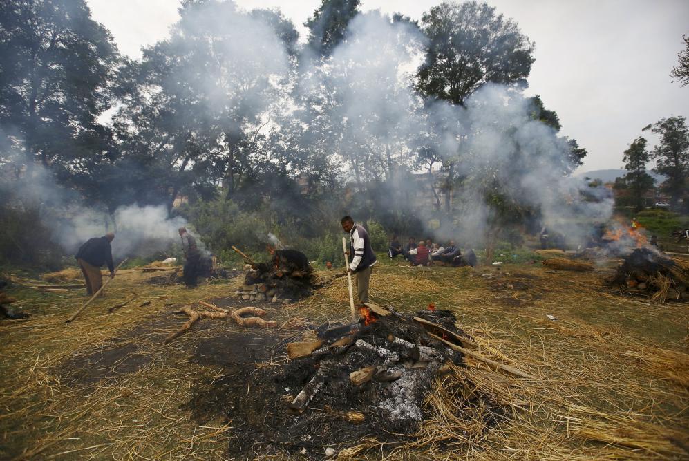 Gente incinerando los cuerpos de las víctimas del terremoto en...