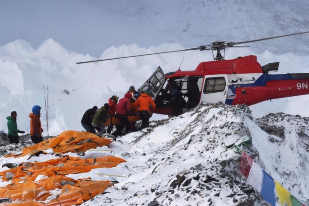 Cargando a una persona herida en el helicóptero en el campo de base a...