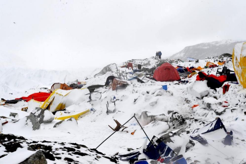 La gente busca sobre la devastación tras una avalancha provocada por...