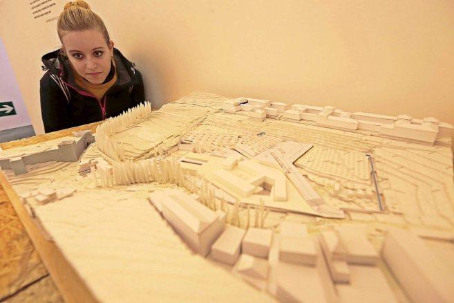 Una joven contempla la maqueta del proyecto de nuevos accesos para la...