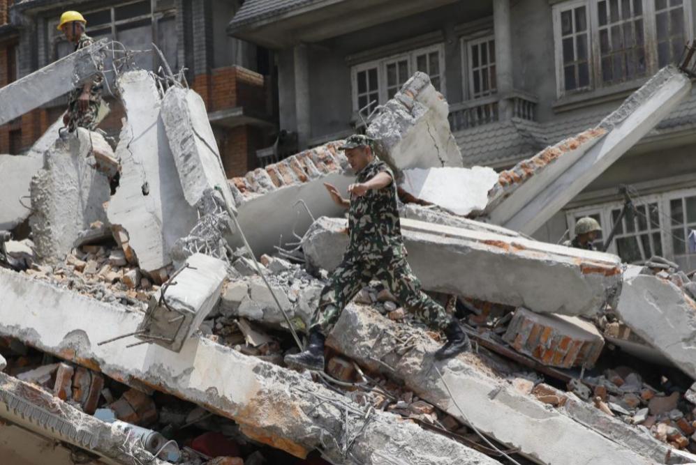 Un miembro del ejército de Nepal busca de sobrevivientes bajo los...