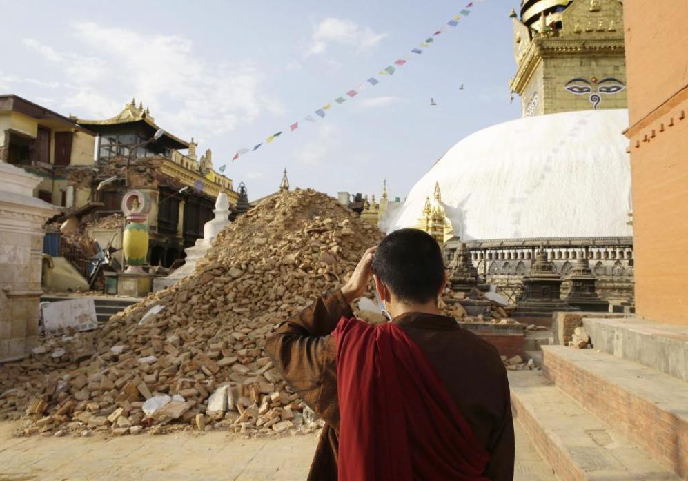 Un monje observa los destrozos producidos por el terremoto en la...