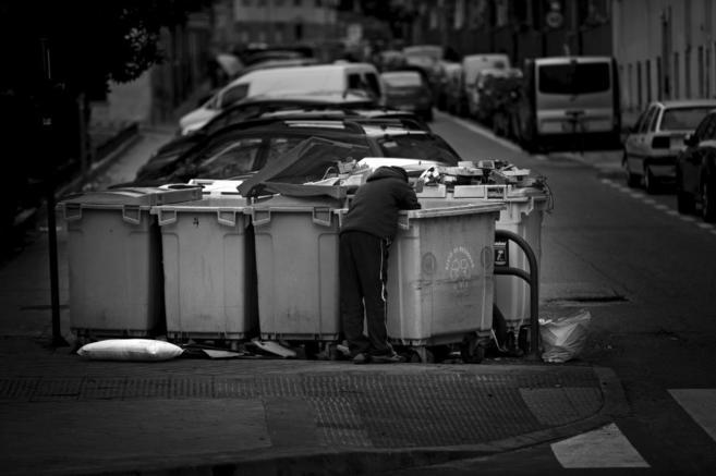 Un hombre busca en las basuras en una calle de Madrid.