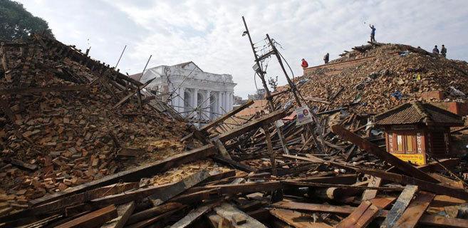 Varias personas caminan sobre las ruinas de un templo de Katmandú.