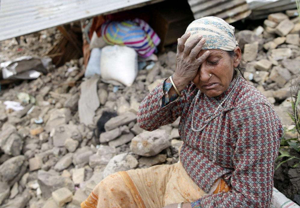Una mujer se lamenta junto a su casa destruida en la aldea de...