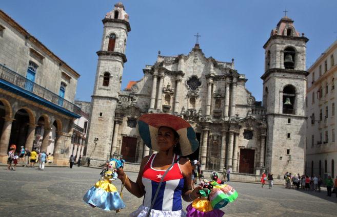 Una mujer vestida con la bandera cubana vende muñecas en La Habana