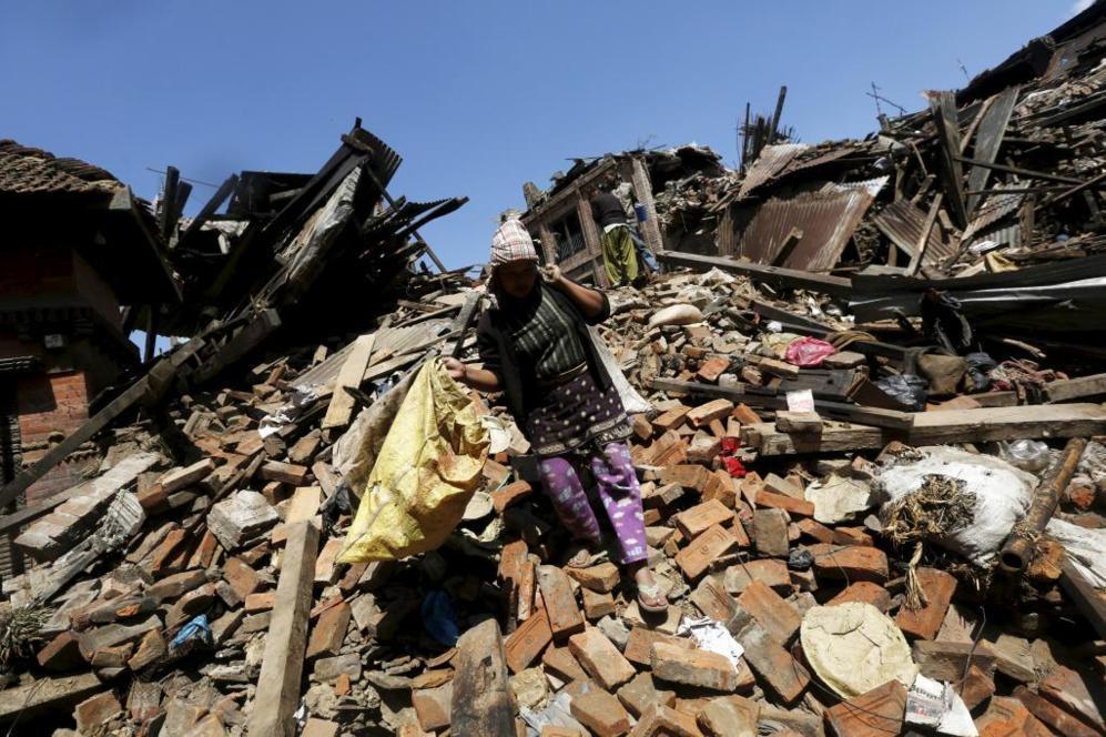 Una mujer acarrea sus pertenencias recogidas de su casa derruida por...