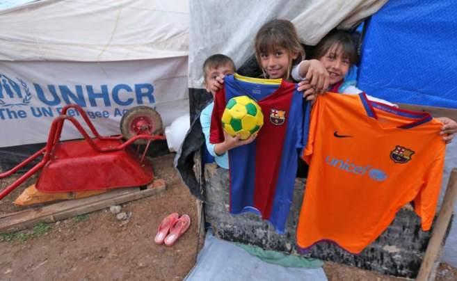 Jóvenes aficionados del Barcelona en un campamento de refugiados...