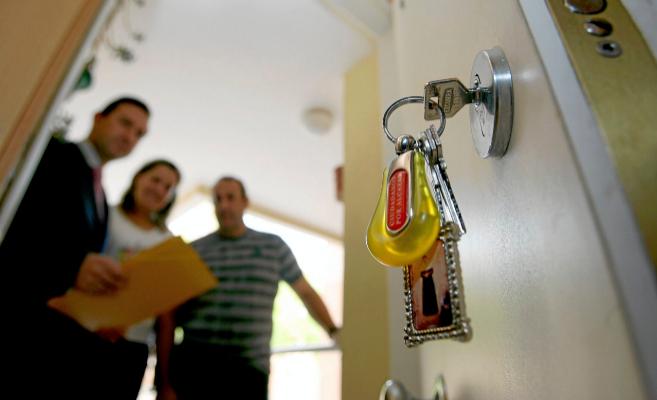 Imagen de los nuevos propietarios en la entrada de su nueva vivienda.