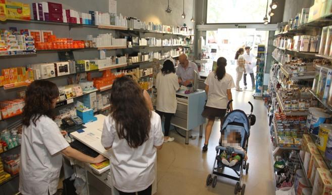 Varios clientes en el interior de  una farmacia de Castellón.