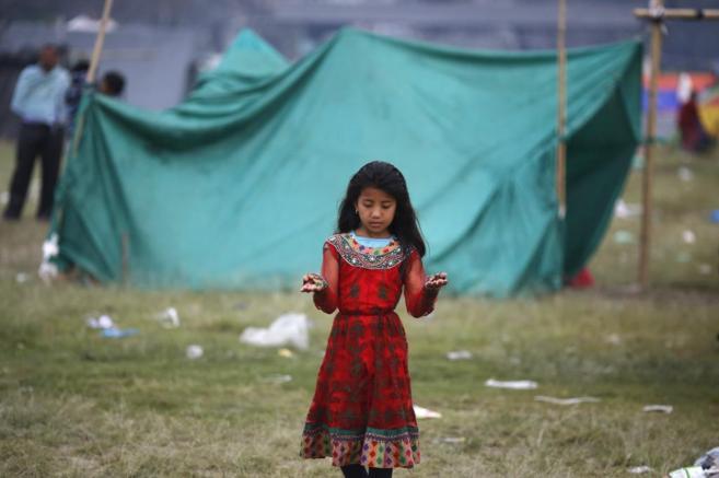 Una niña nepalí, ante una de las carpas donde se han refugiado...