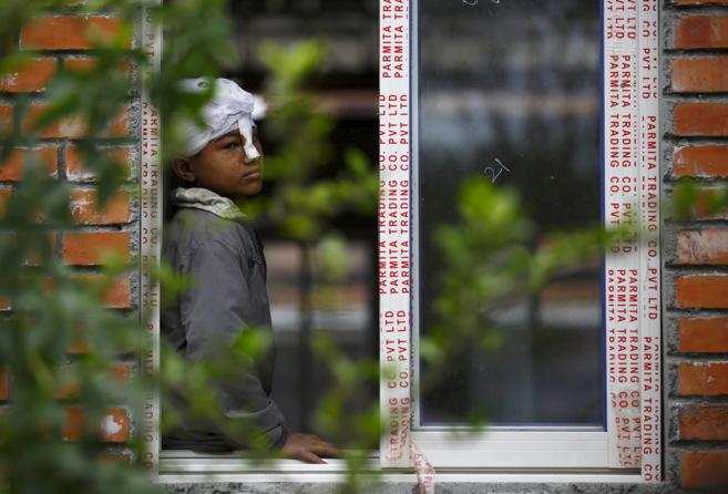 Un niño herido en el terremoto mira hacia fuera desde la ventana de...