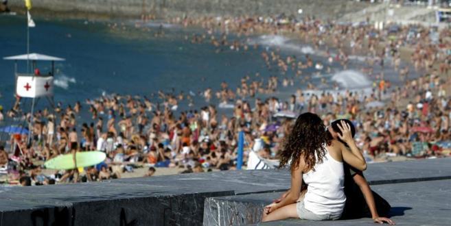 Una pareja de jóvenes  se besa en la playa de Ondarreta de San...