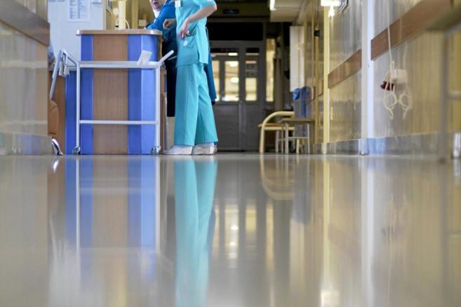 Una sanitaria atiende a las preguntas de un paciente en el pasillo de...