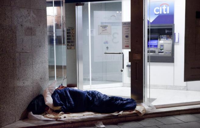Un mendigo duerme junto a una entidad bancaria en Madrid.