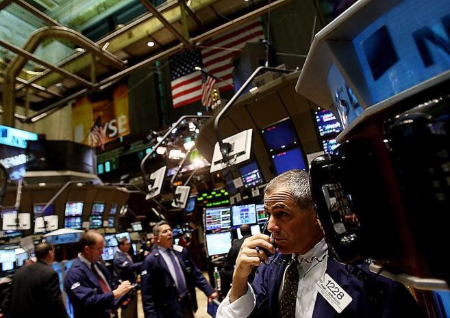 Un grupo de 'brokers' atienden las pantallas y las llamadas...