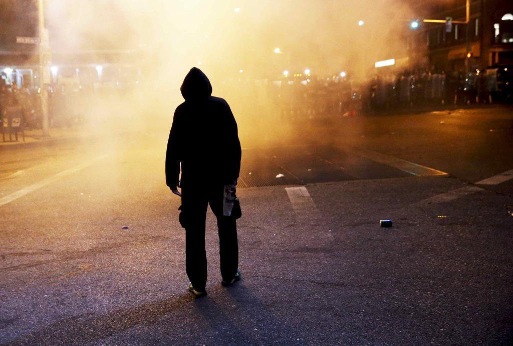 Un manifestante frente al despliegue policial tras el toque de queda.