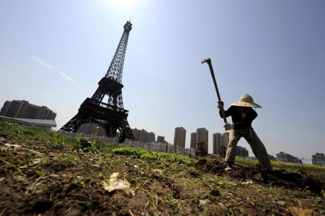Un campesino chino trabaja la tierra ante la réplica de la Torre...