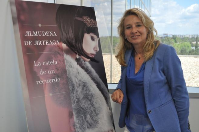 La escritora Almudena de Arteaga junto al cartel de su última novela.