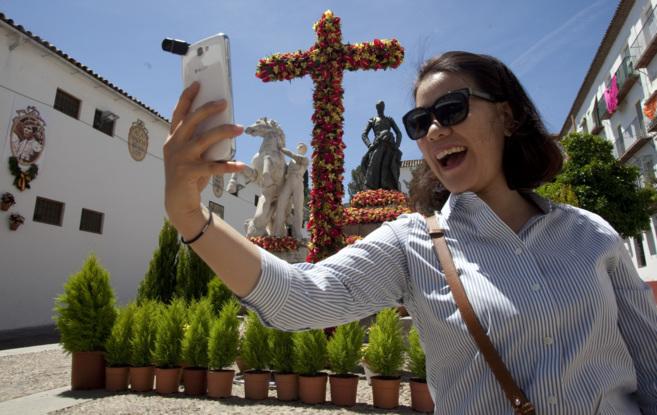 Una joven se hace una foto junto a una de las cruces instaladas en una...