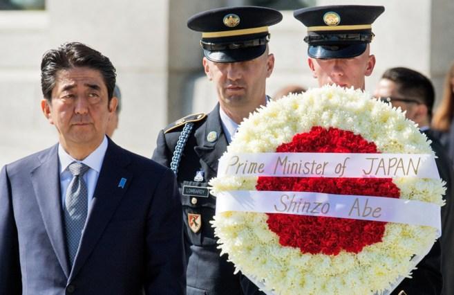 El primer ministro japonés se dispone a depositar flores en el...