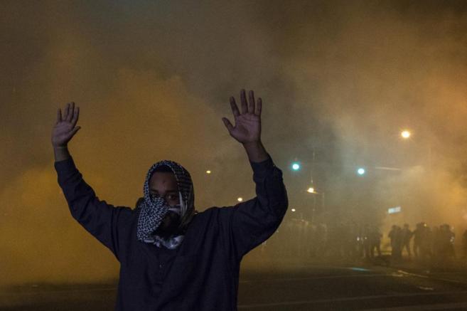 Un manifestante levanta los brazos entre nubes de gas lanzado por la...