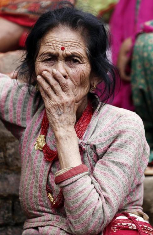 Una mujer observa los escombros de los edificios destruídos tras el...