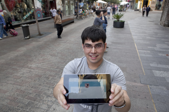 Uno de los promotores muestra la aplicación en una calle comercial...