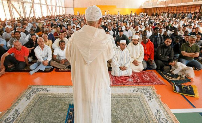 Un imam se dirige a los fieles en una multitudinaria celebración de...