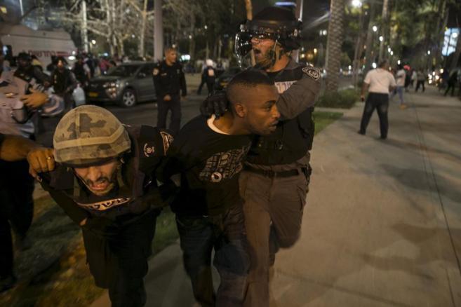 Un joven etíope es detenido por un agente tras la protesta contra la...