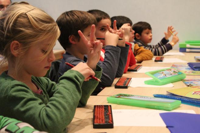 Varios niños aprenden a sumar con este procedimiento en clase.