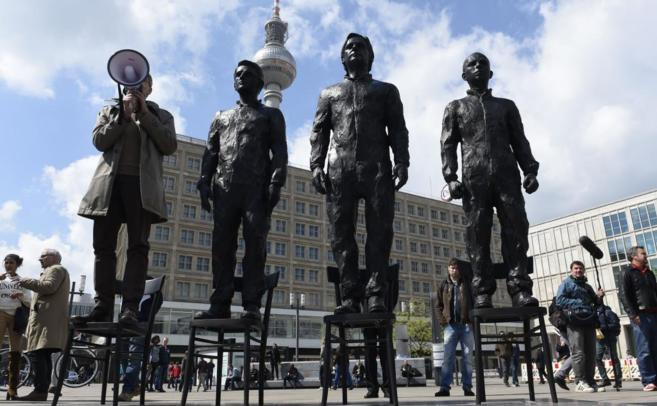 Un hombre junto a tres estatuas de Edward, Julian Assange y Chelsea...