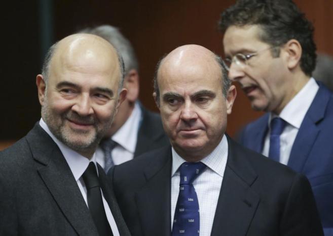 El ministro de Economía, Luis de Guindos (izda), junto al comisario...