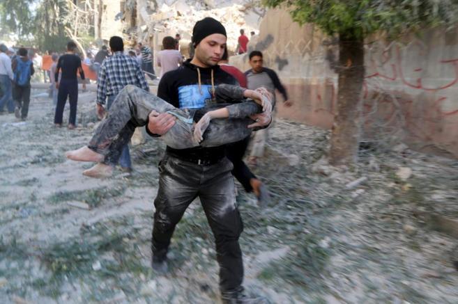 Un hombre rescata a un niño tras un bombardeo en una escuela, en la...