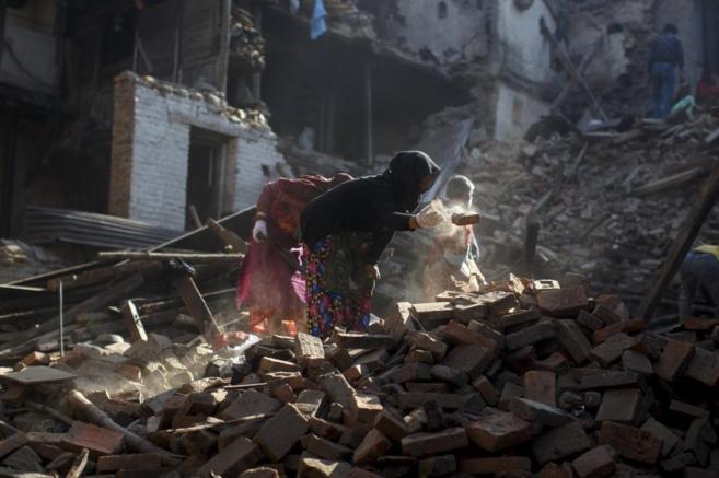 Nepalíes limpian de escombros sus casas tras el terremoto, en...