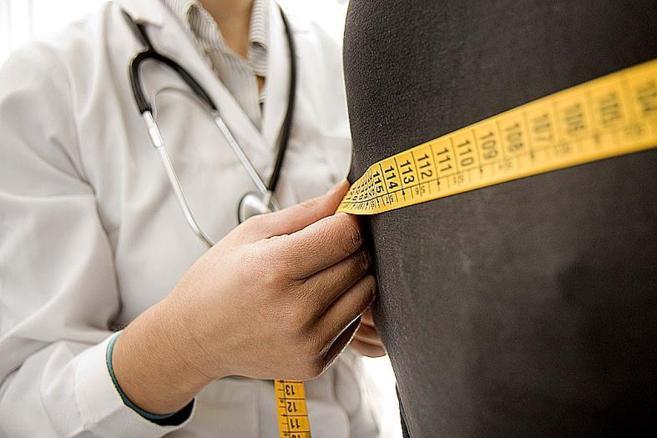 Un médico mide el perímetro abdominal de una persona con sobrepeso.
