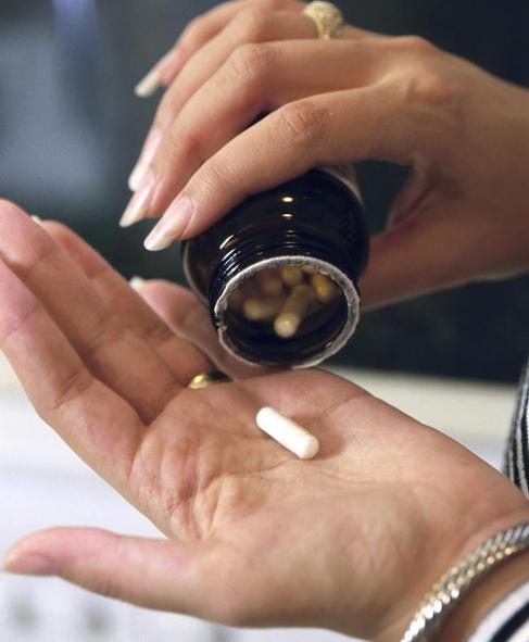 Una mujer con un bote de pastillas.