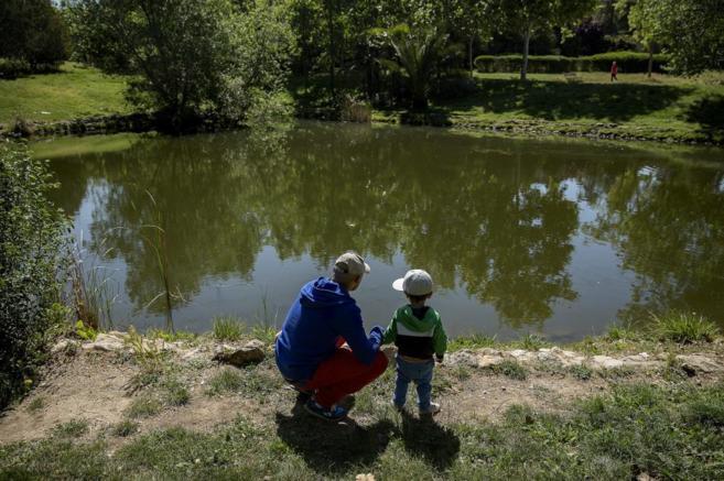 Un padre pasea con su hijo por el parque de Las Tres Cruces, en...