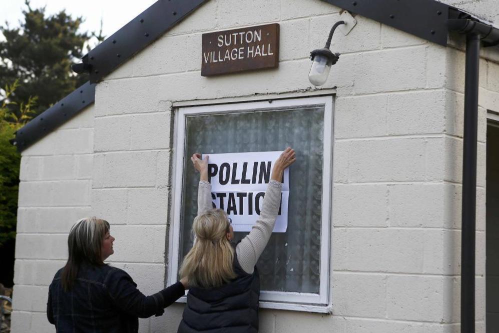 Dos mujeres ponen un cartel en un edificio usado como colegio...
