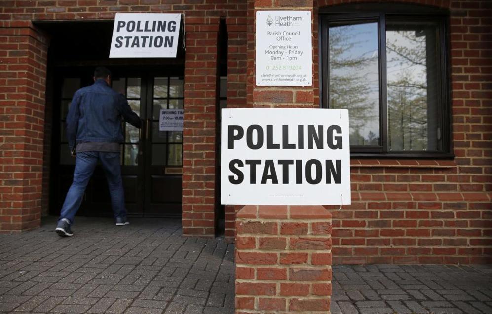 Un hombre entra en un colegio electoral en Elvetham Heath, al sur del...