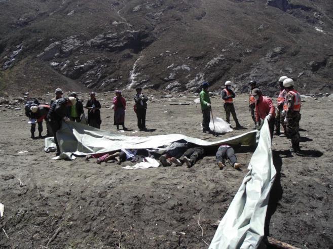 Miembros de un equipo de rescate cubren los restos mortales de...