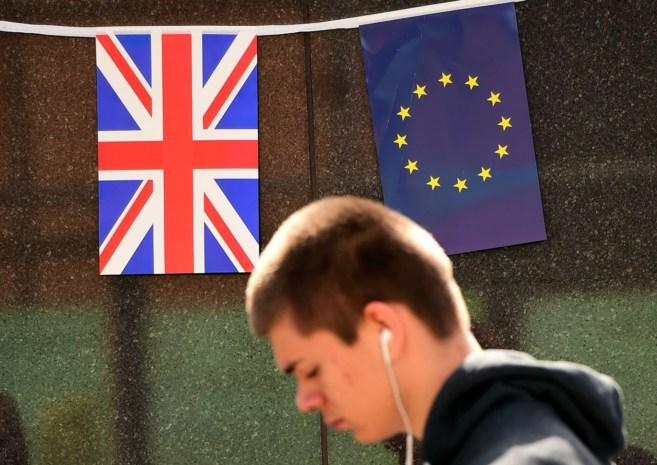 Un joven pasa ante las banderas europea y británica en la sede de la...