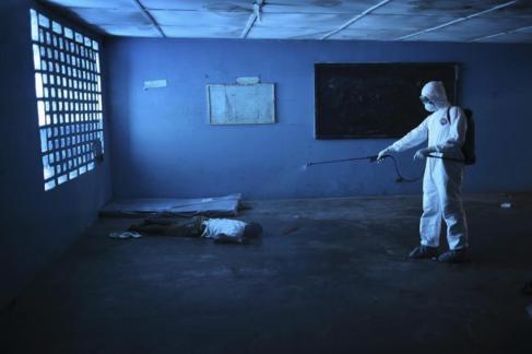 Un trabajador sanitario desinfecta un cadáver en Monrovia, Liberia.