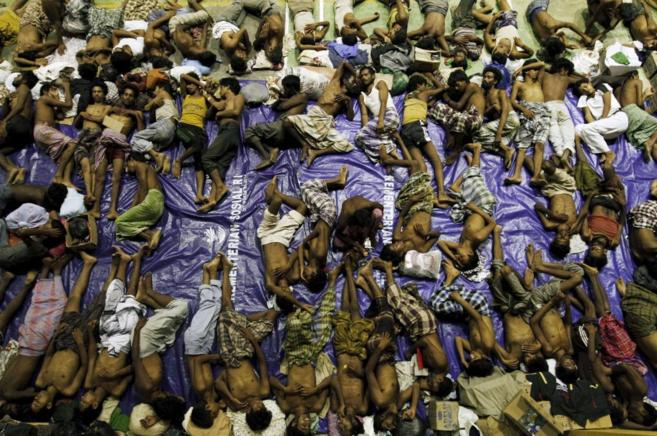Parte de los inmigrantes rescatados descansan tras ser socorridos.