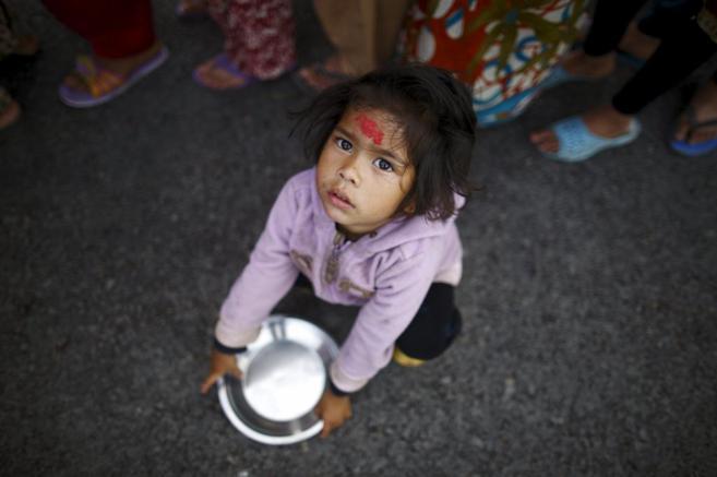 Una niña nepalí, en una cola para conseguir comida, en Katmandú.
